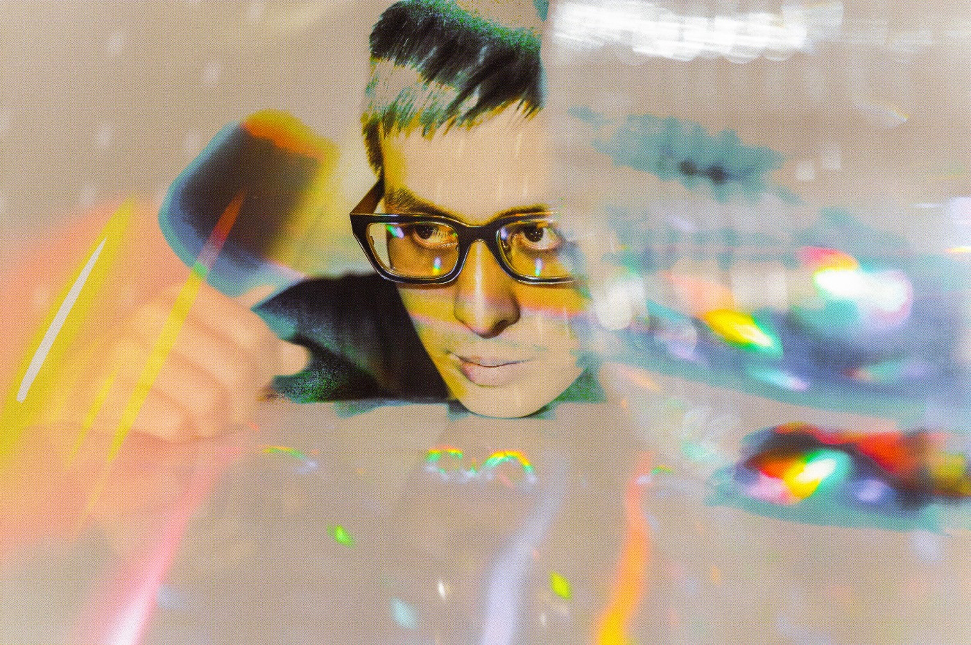 Photograph of a white, non-binary person wearing glasses with short hair. They are resting their chin on a table and look frustrated. The photo is abstract with blurry swipes, dots and other shapes overlaid on the image.
