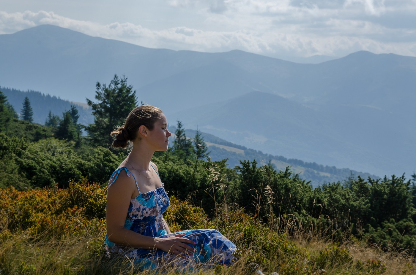 A young woman sits on a sunny hill side while meditating