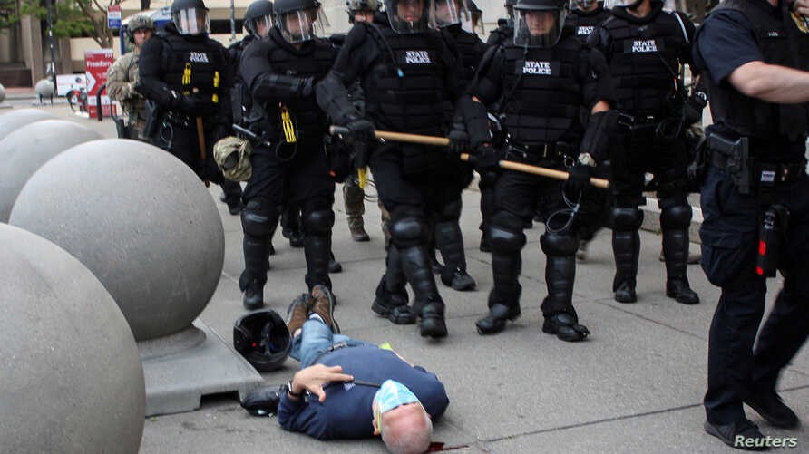 Martin Gugino bleeds on the ground after being pushing by a Buffalo police officer as officers in riot gear walk past him.