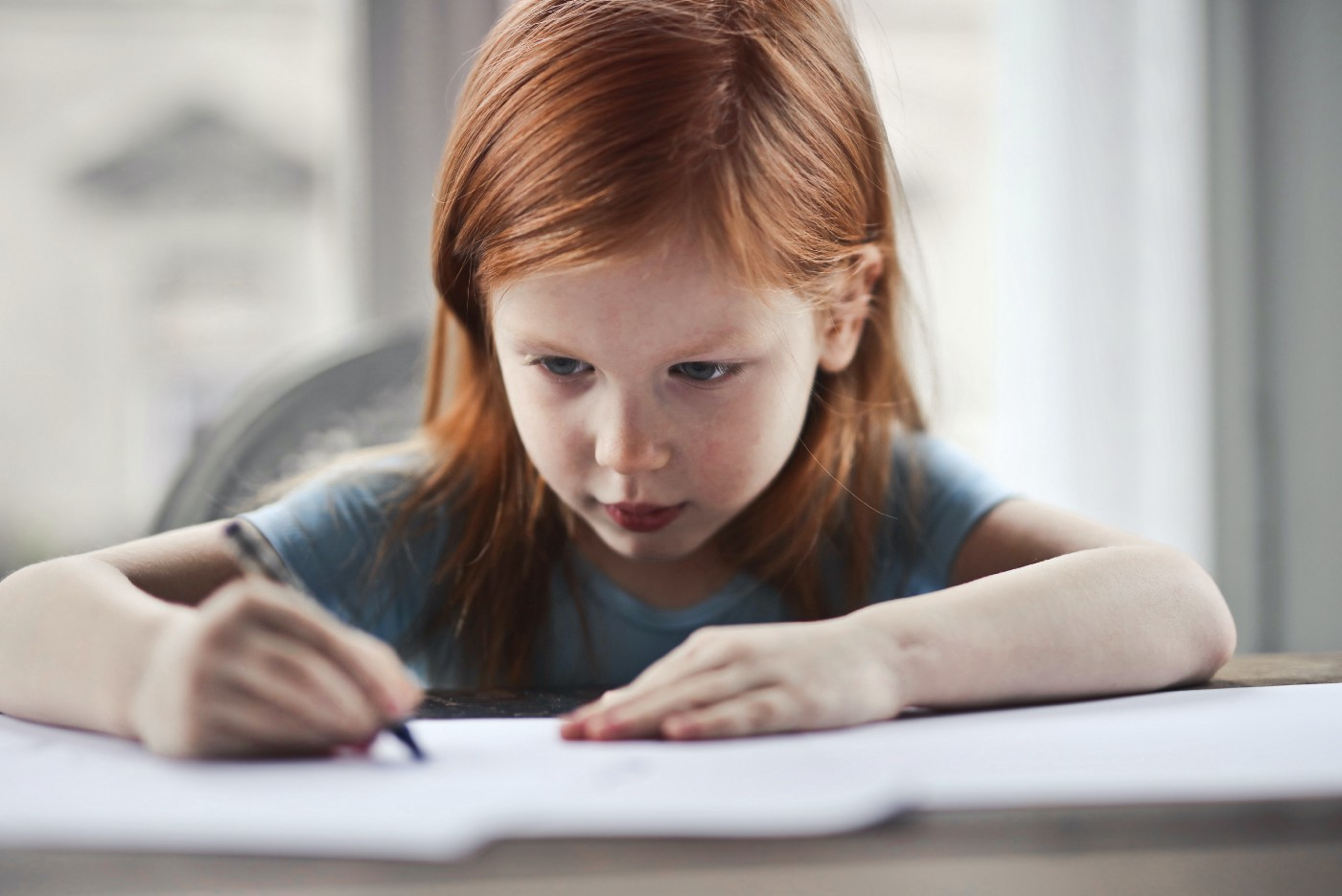 A little girl writing on paper