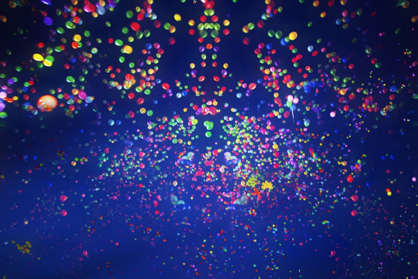 Many multi-colored balloons in the dark sky.