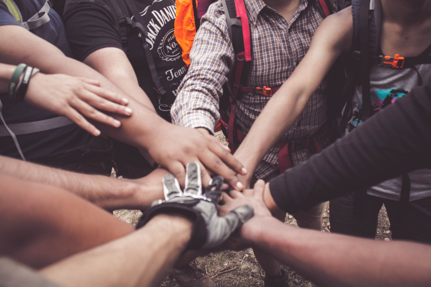 Photo of a group with all their hands reaching towards the middle in a huddle.