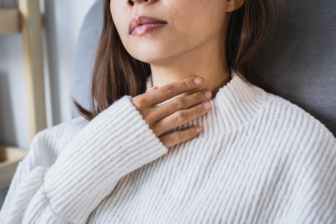Photo of a woman putting her hand to her collarbone