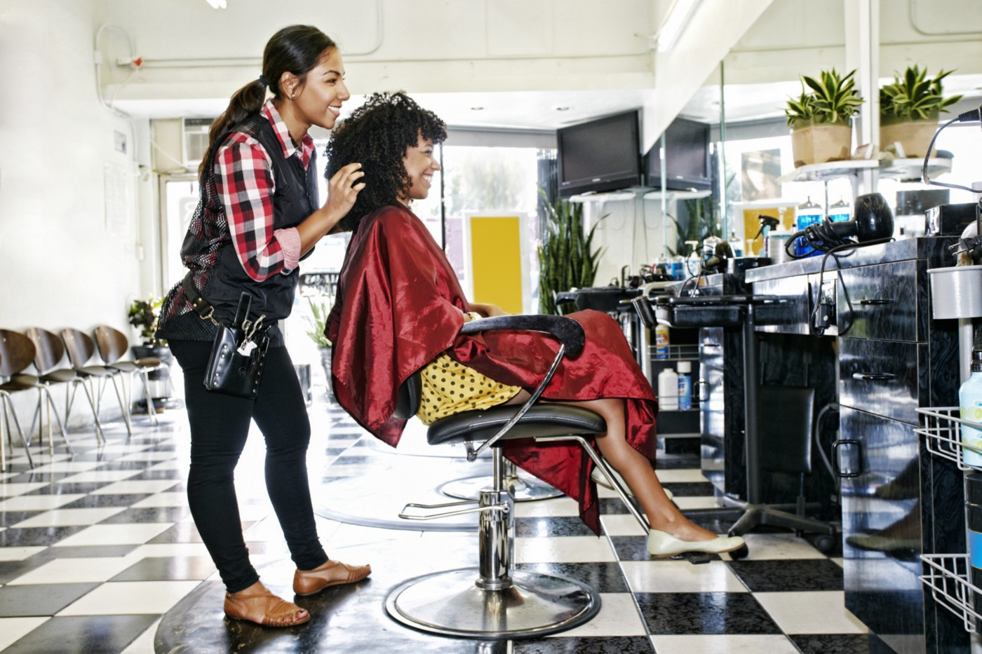 A photo of a black woman getting her hair done by a woman of color at a hair salon.