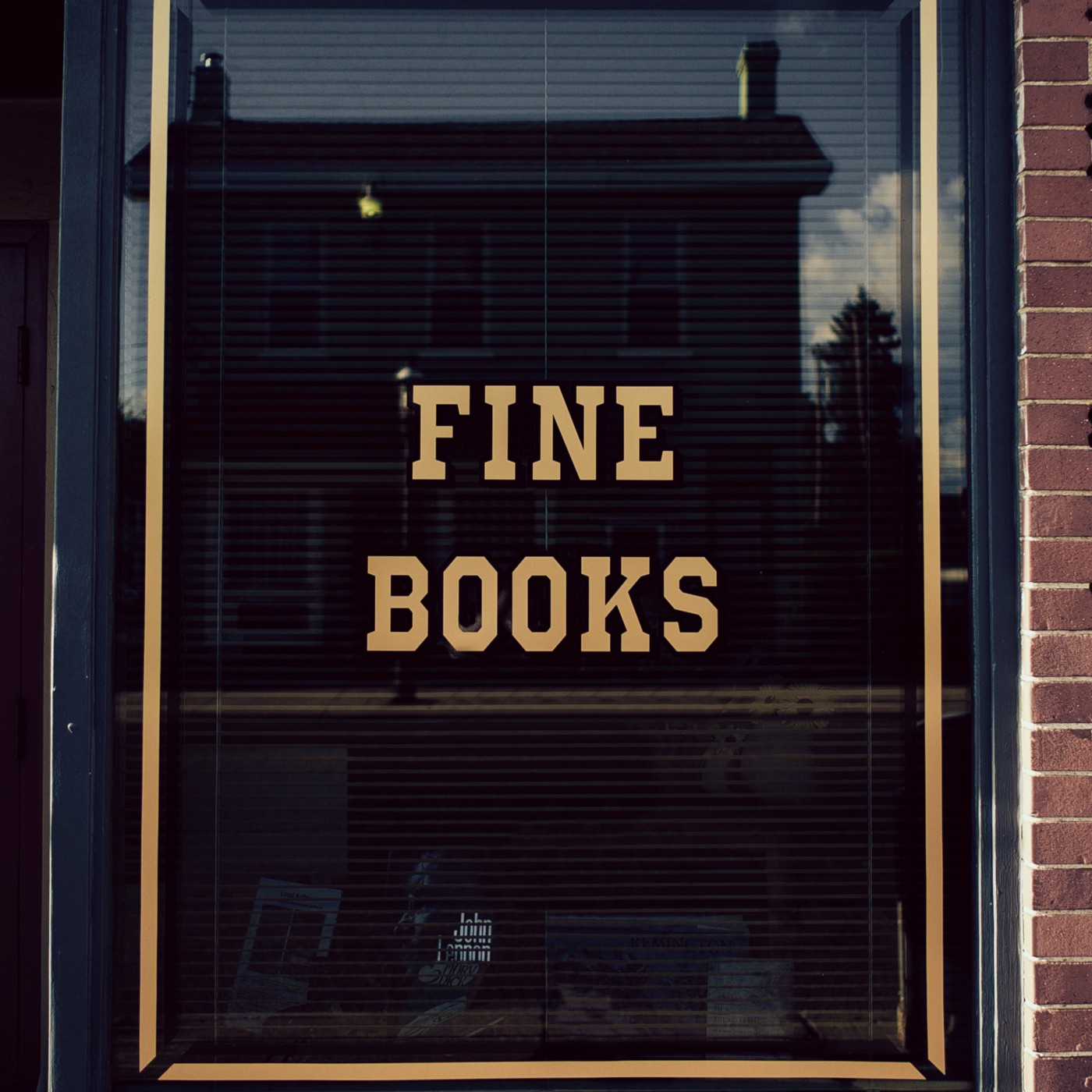 """[image description: a glass window with the words """"fine books"""" in gold.]"""