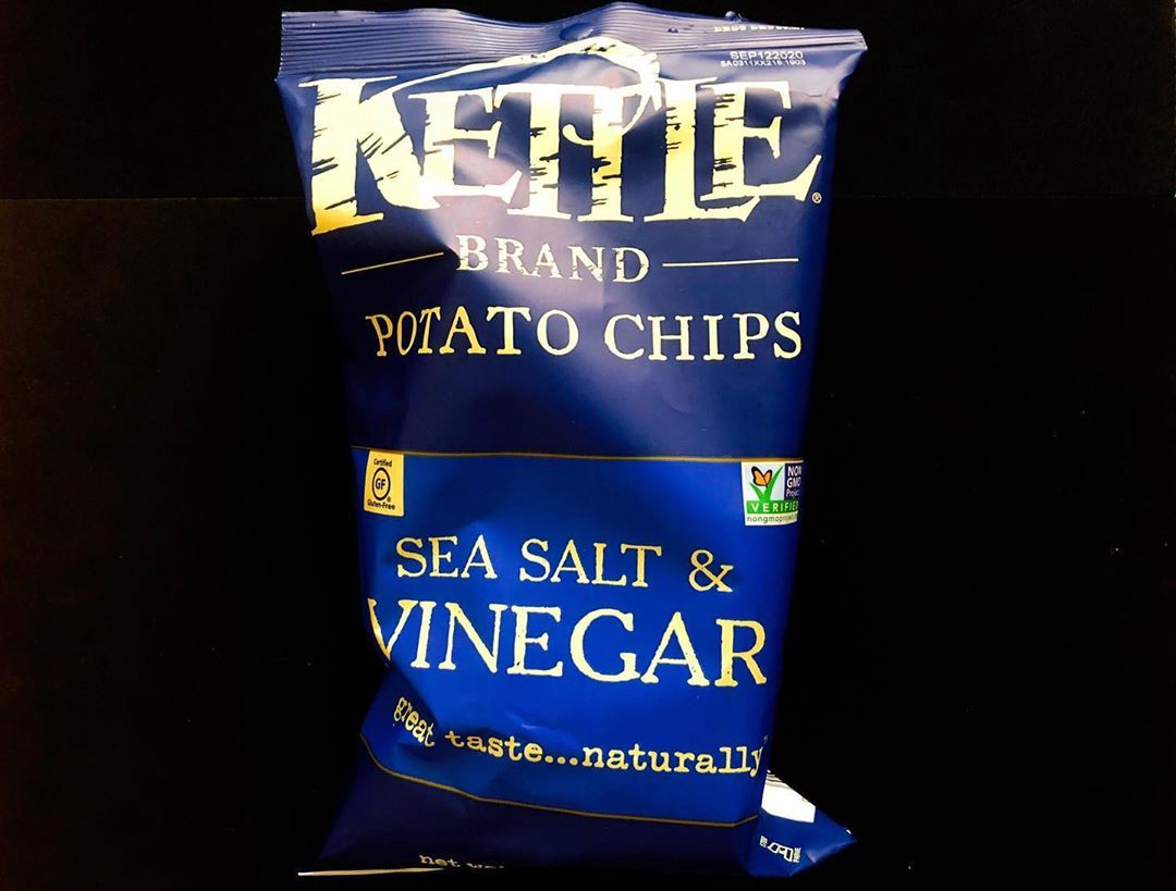 A blue bag of Kettle Brand Sea Salt and Vinegar chips isolated on a black background.
