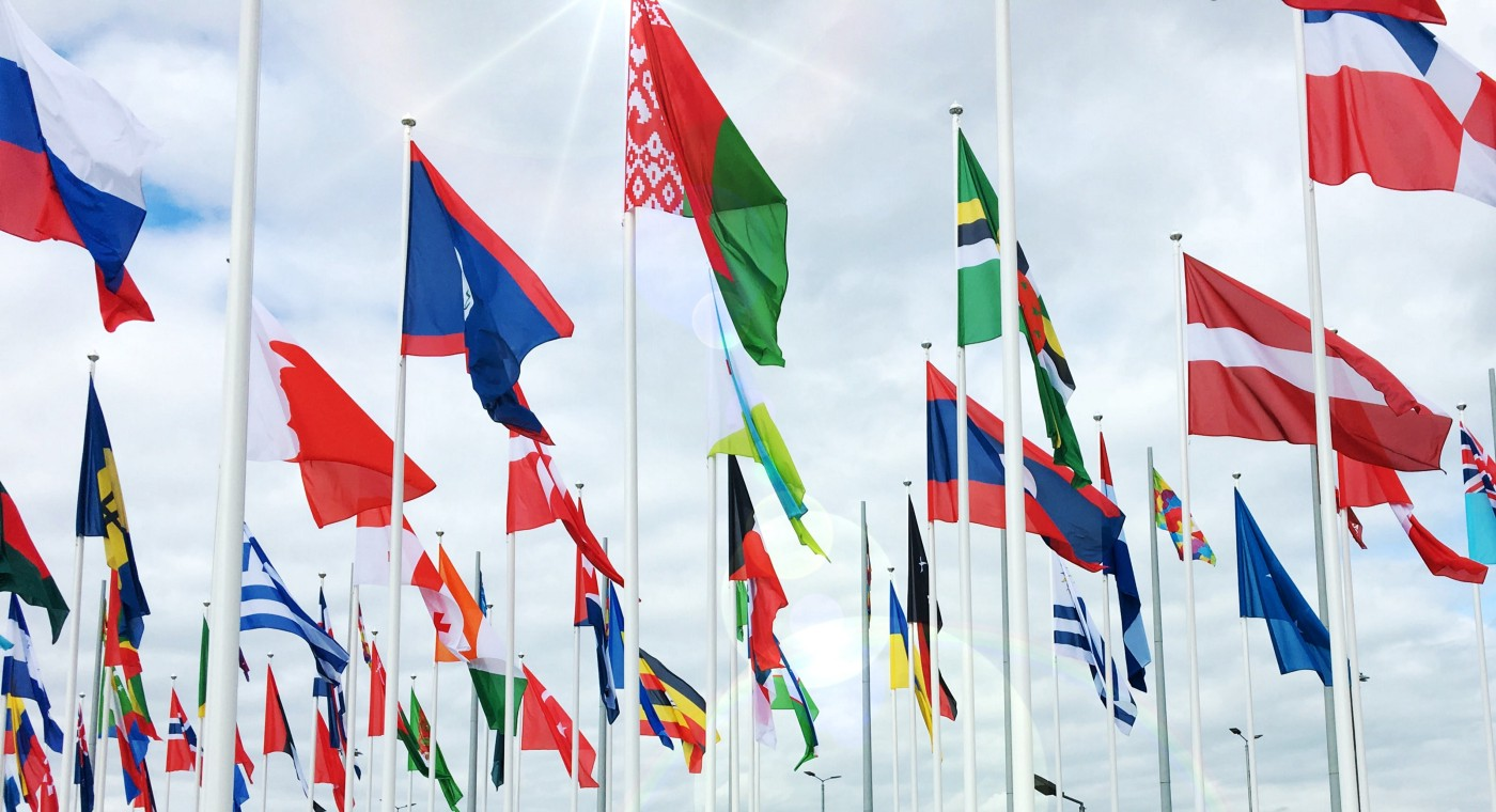 World flags from many countries against a cloudy sky.