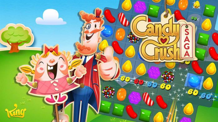 Two characters of Candy Crush Saga's eccentric cast beam and give thumbs up beside the game's title and token candy grid.