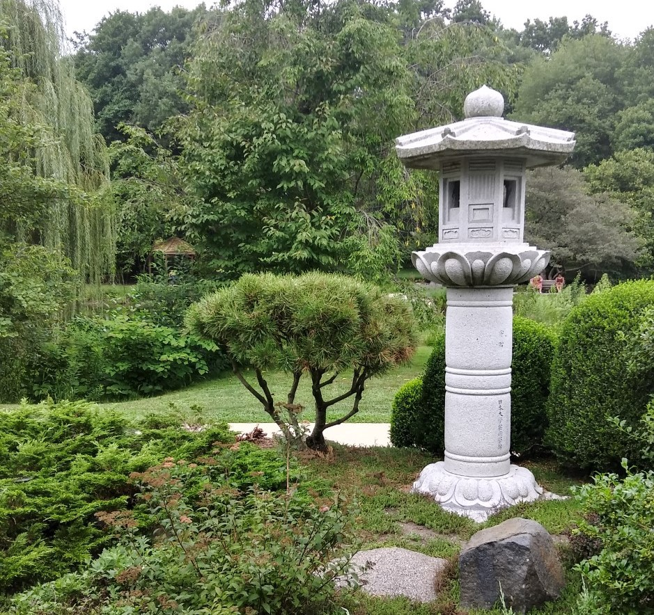 A stone pagoda amid weeping willow, bonsai tree and various shrubs at the Japanese Garden in Champaign-Urbana, IL.
