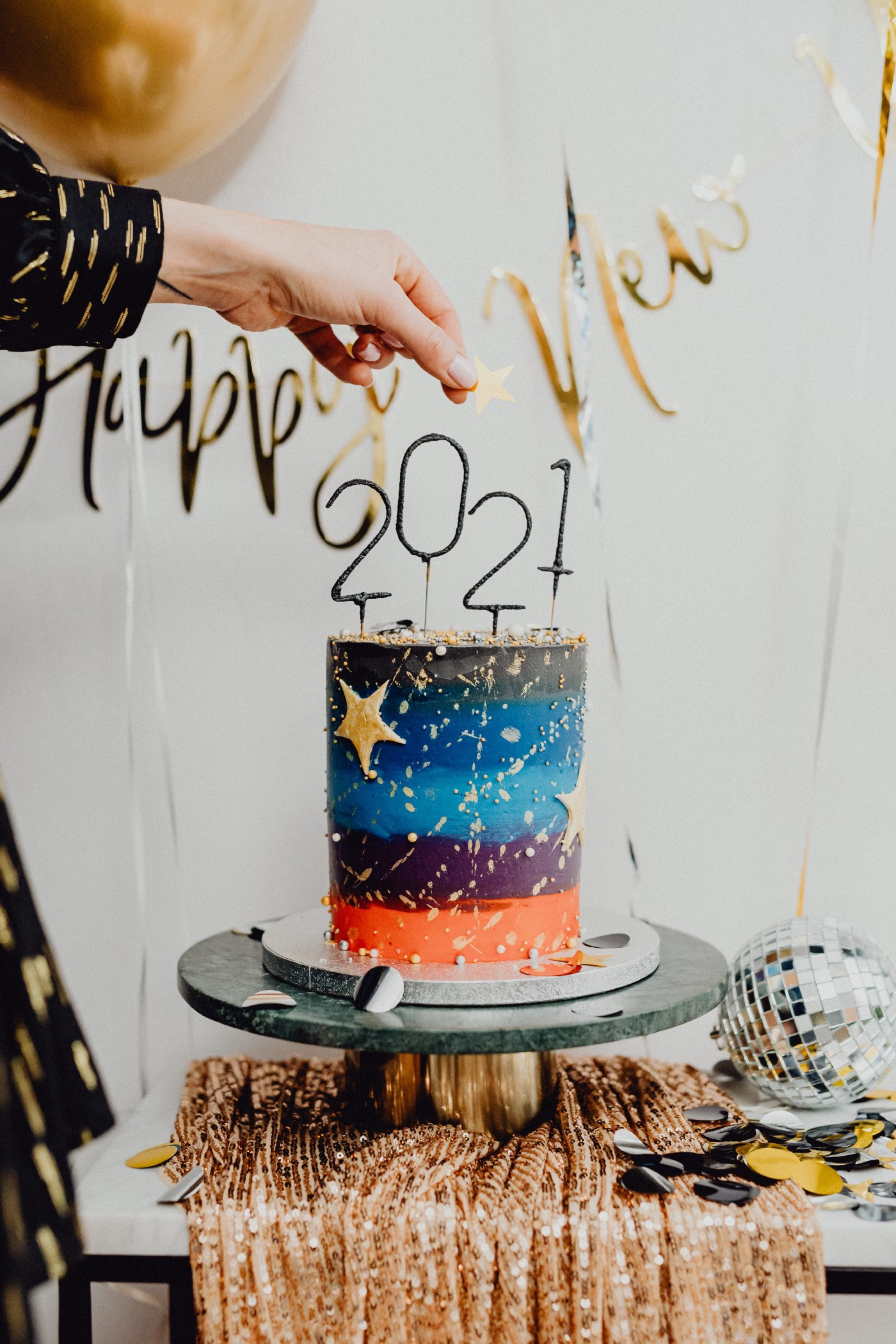 "A colorful tall cake with ""2021"" on top if it and the words ""Happy New Year"" above the cake."