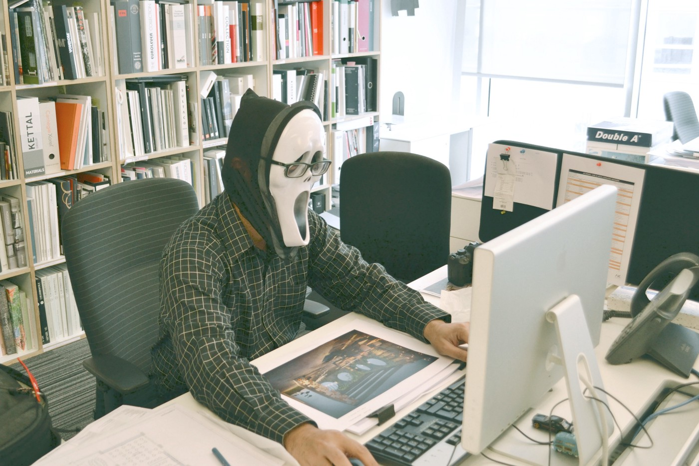 Man wearing a halloween mask and eyeglasses on his office computer