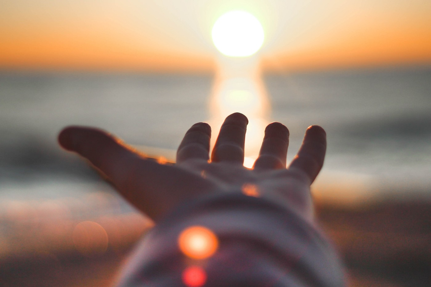 Photo by Todd Rhines on Unsplash • open-palmed hand reaching toward the sun rising on the horizion