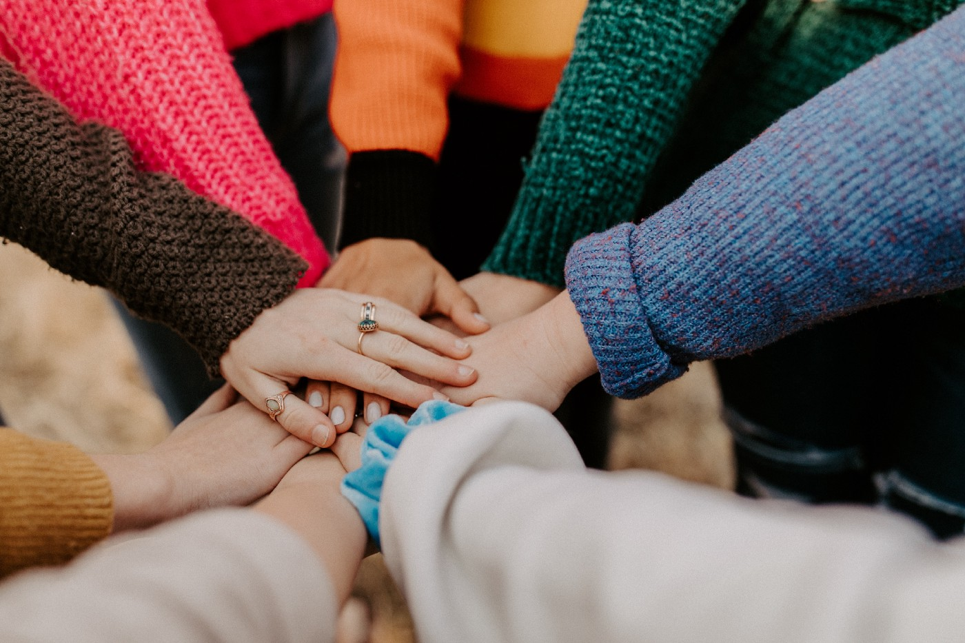 Photo of multiple people placing their hands on top of one another in a gesture of solidarity.
