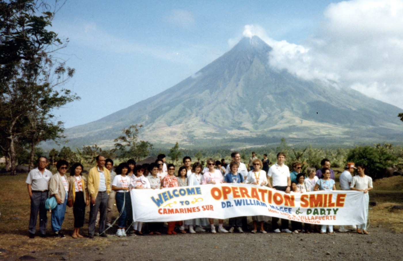 A group poses in front of a mountain in the Philippines during the first-ever Operation Smile mission.