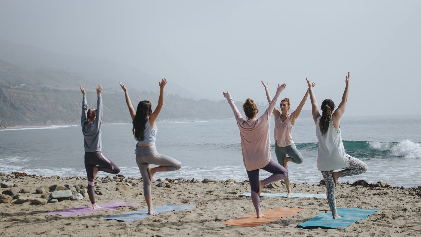A group of women doing yoga on a beach