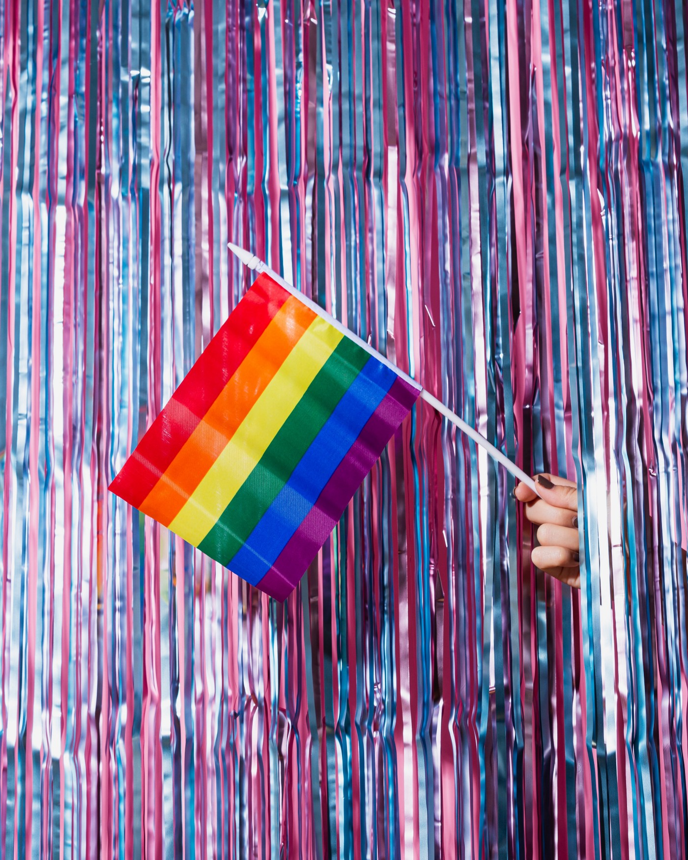 A small pride flag held from beyond a shiny curtain