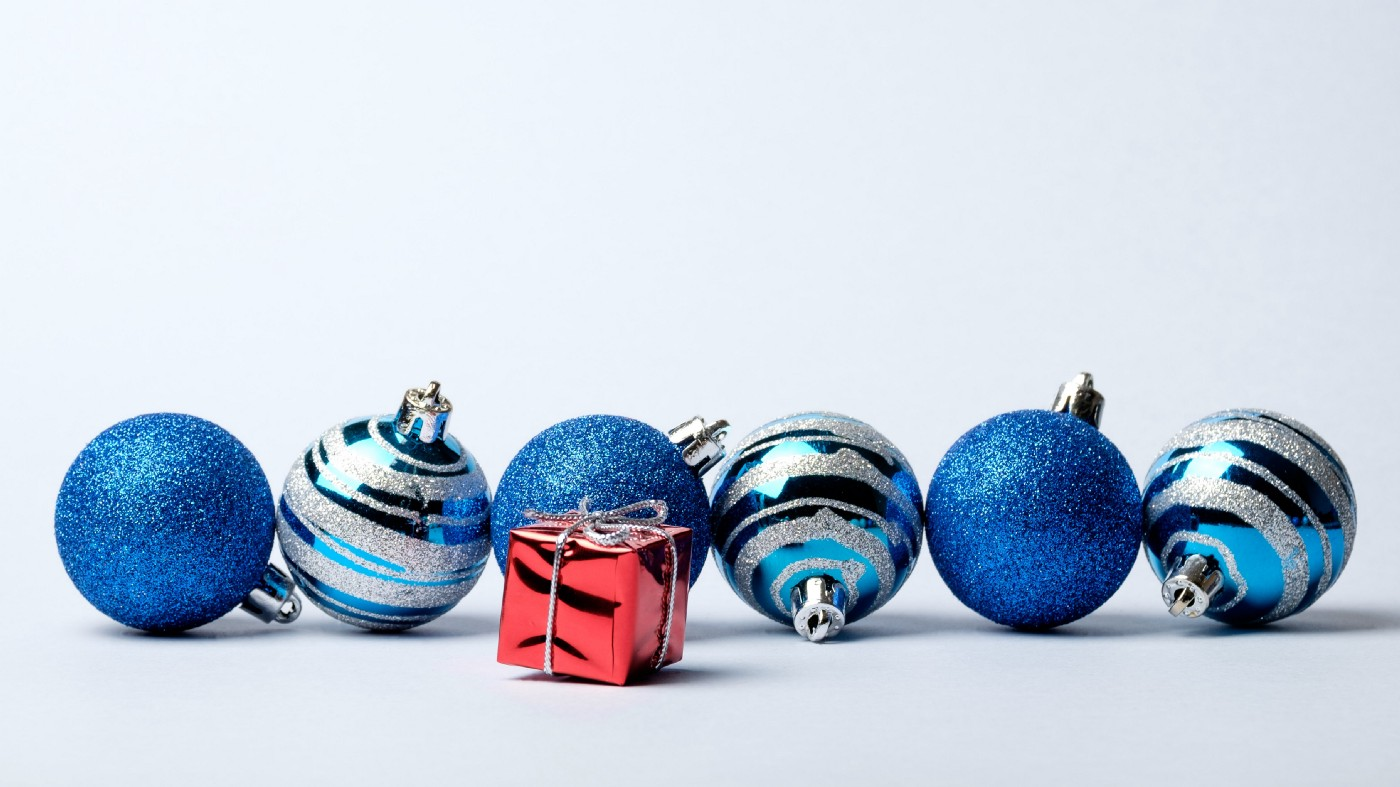 Assortment of blue Christmas ornaments with small red package.