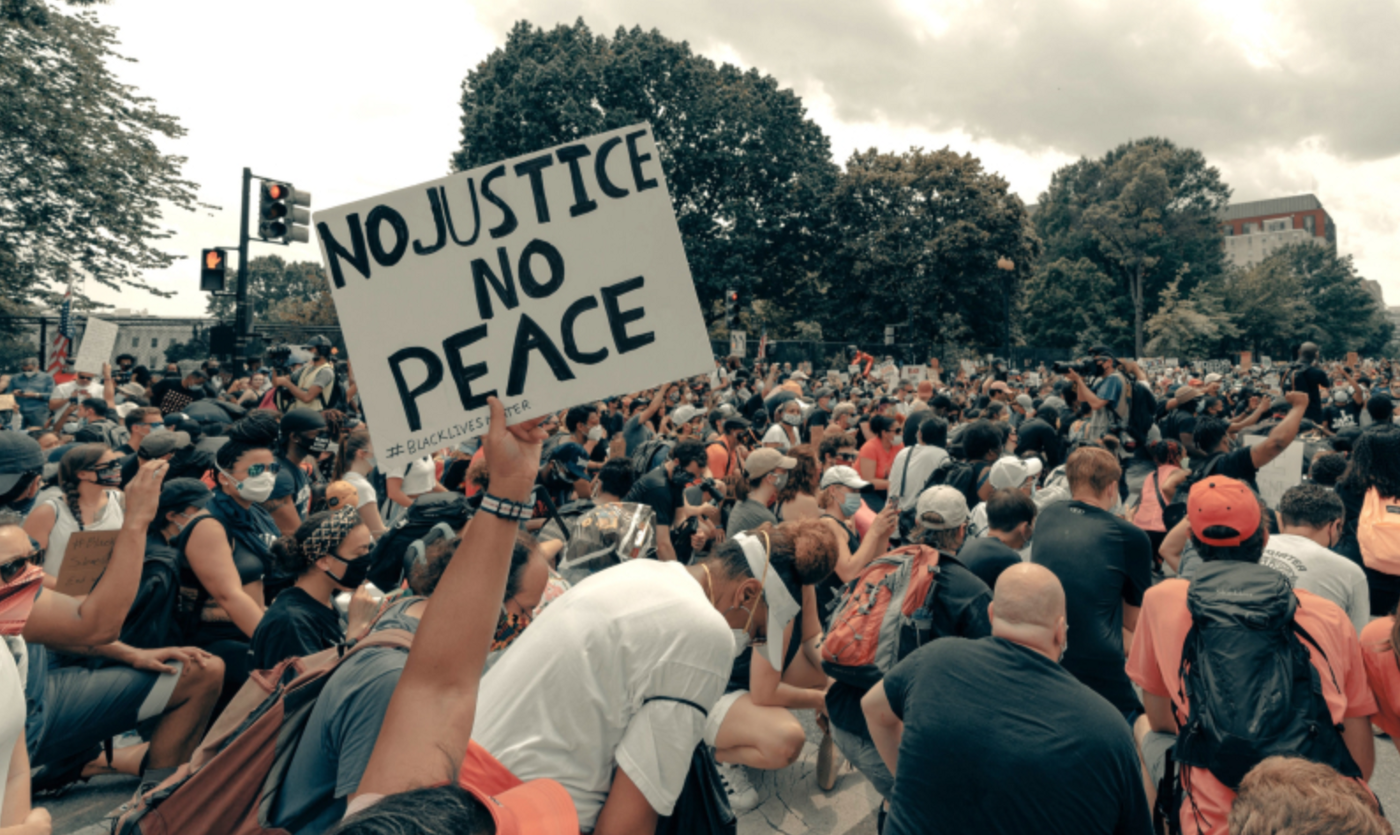 "Protesting crowd with one person holding a sign, ""No Justice No Peace"""