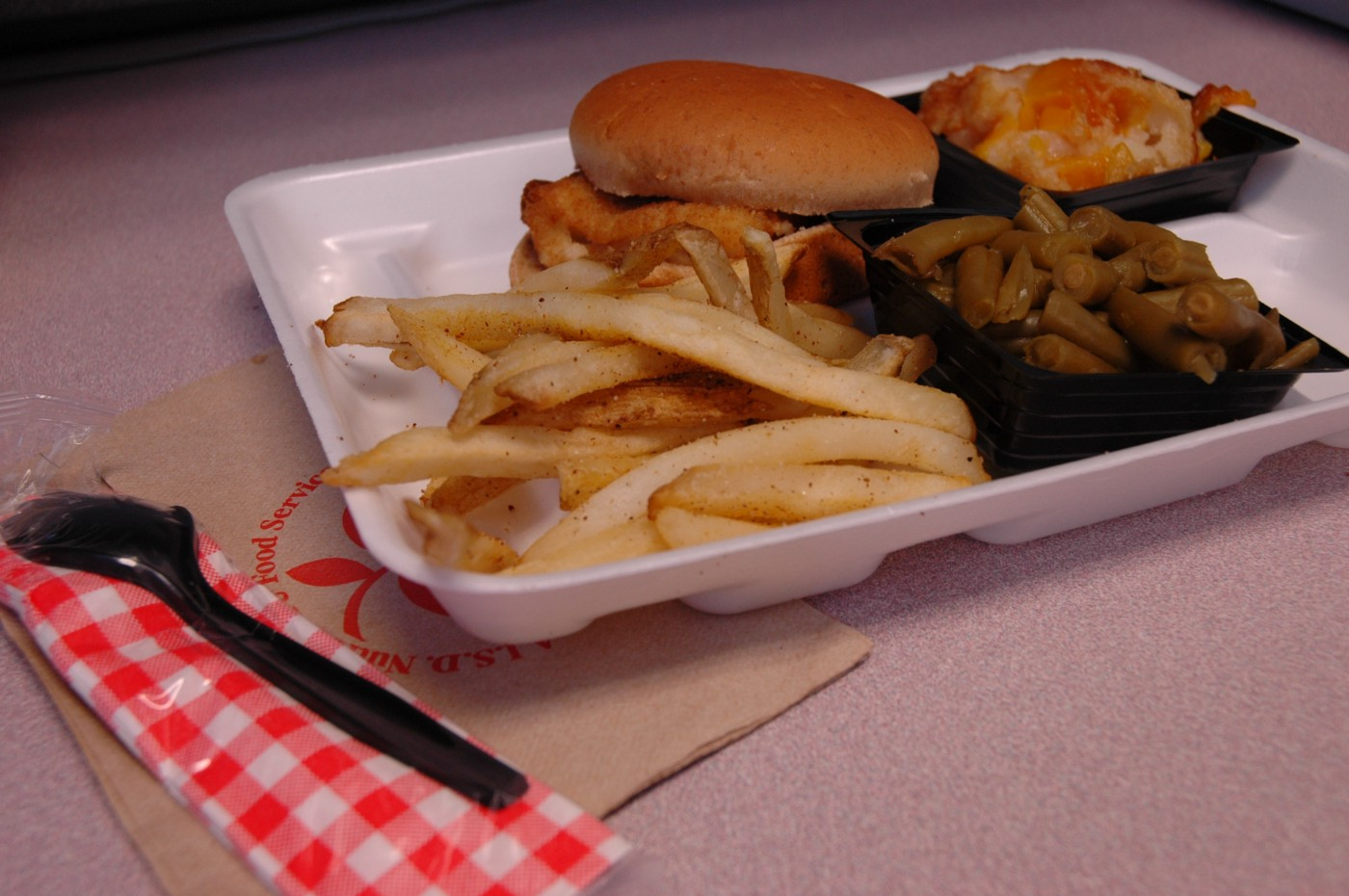 school lunch in a styrofoam tray including a fried chicken sandwich, french fries, and green beans