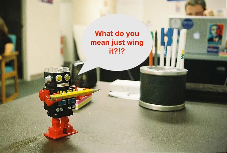 "Toy robot holding a pencil and saying ""What do you mean just wing it?"""