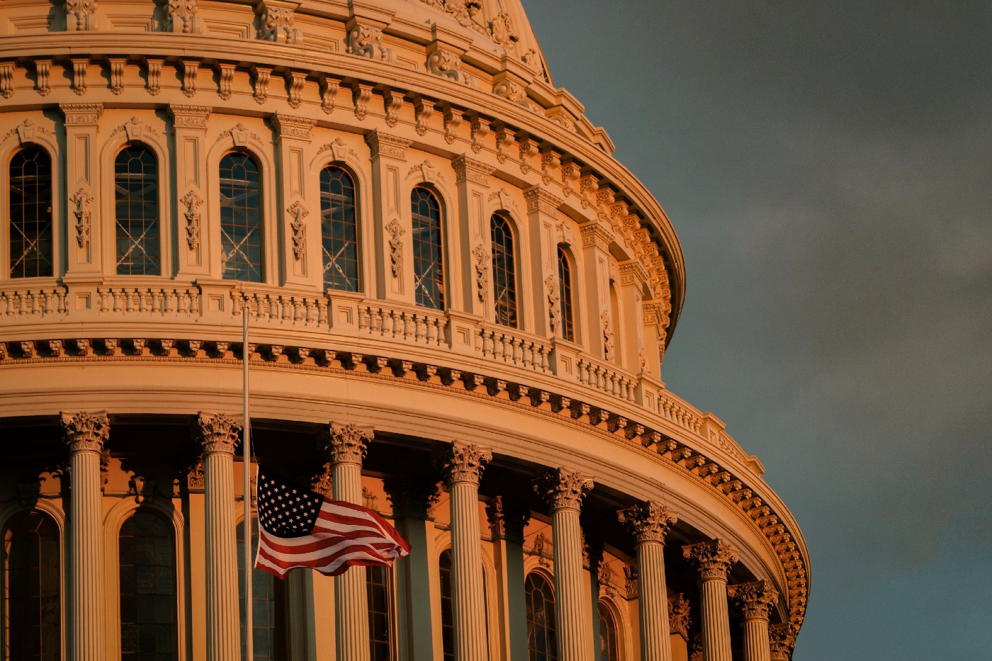 Close up of columns in the dome of the US national capitol building with flag waving at half-mast at sunset