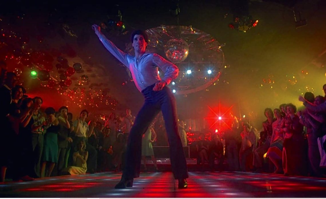 Still of Saturday Night Fever with John Travolta posing in disco with crowd