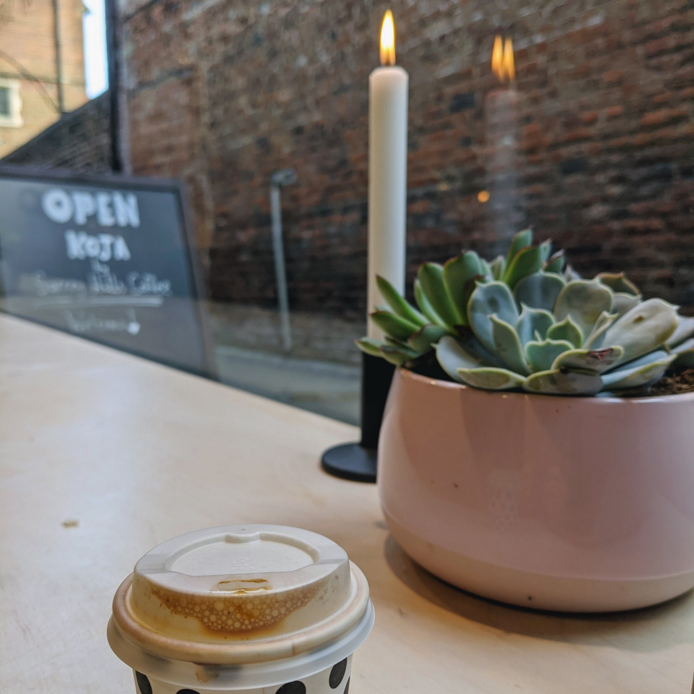 A coffee shop table with a coffee cup, a candle and a plant. In the background, a sign says that the cafe is open.
