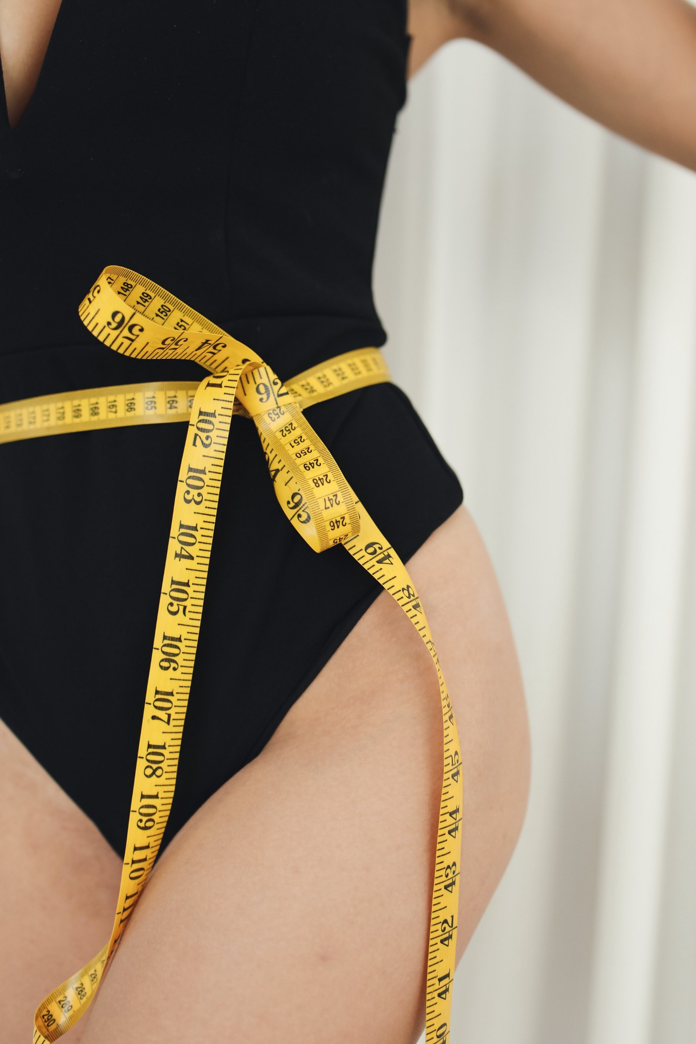 A measuring tape tied around a waist because of a fat flaw
