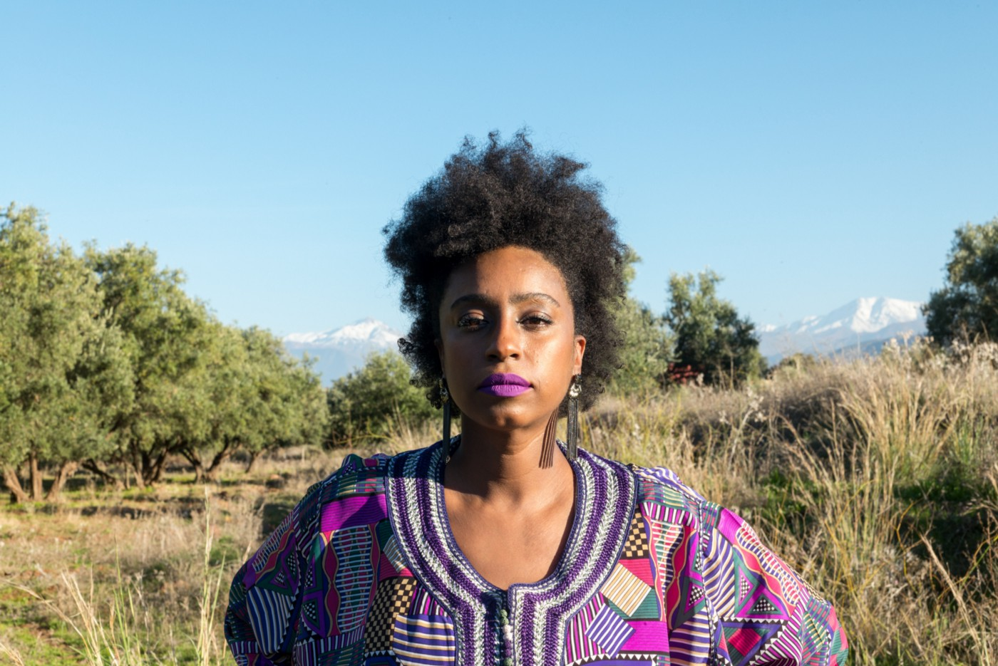 A confident Black woman standing against a prairie-like background.