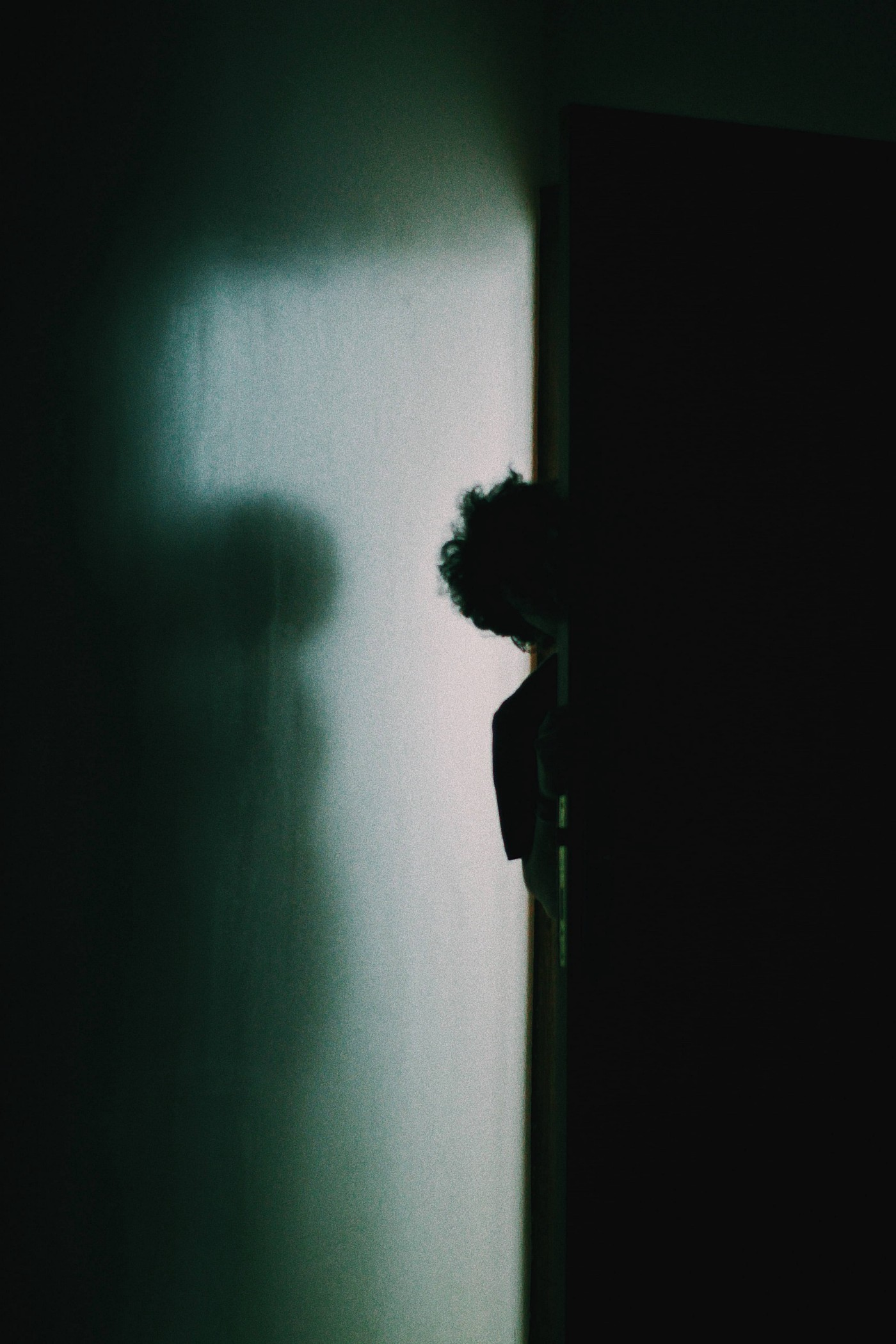 Photo Credit: Ammar Sabaa/Unsplash. A barely lit hallway and completely dark room. A boy shyly peeks around the corner of the dimly lit hall into the dark room.