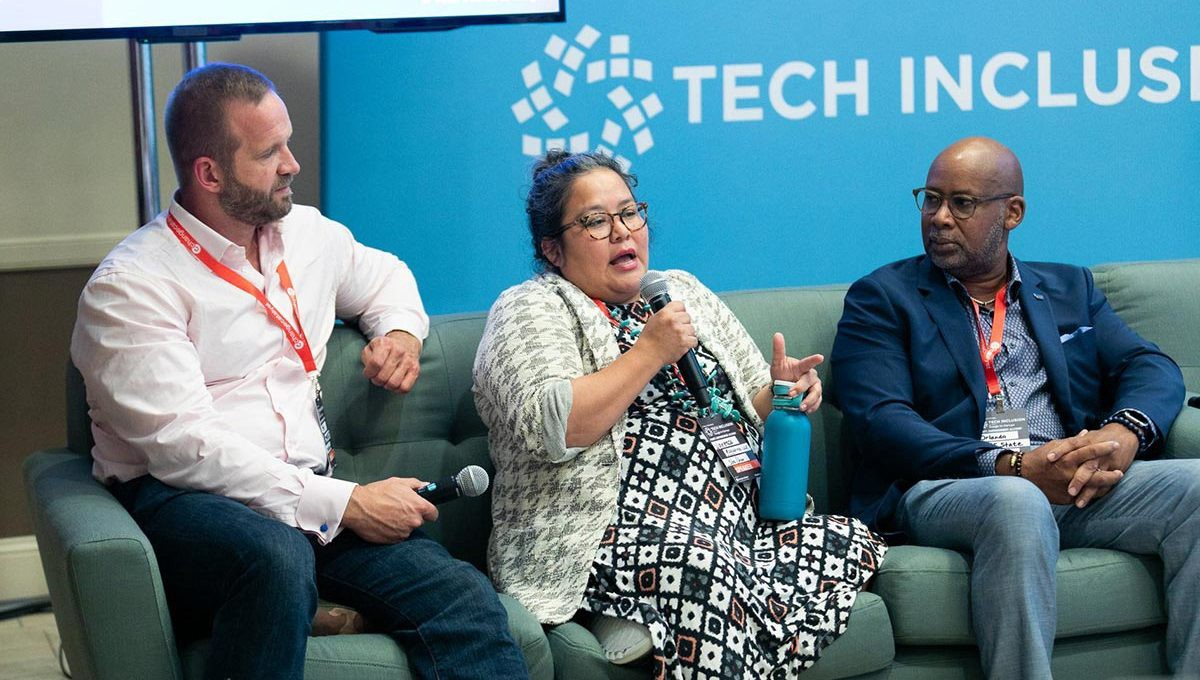 Three people sit on a couch in front of a blue Tech Inclusion sign, discussing inclusion ecosystem building for a panel.