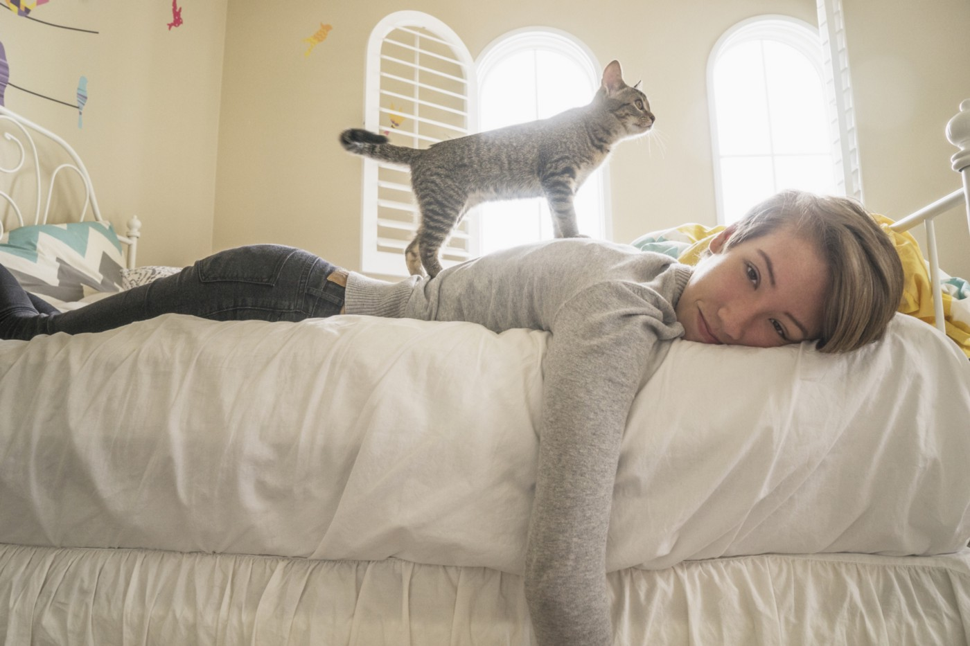 A young woman lies languidly in bed on her stomach while a cute cat stands on her back.