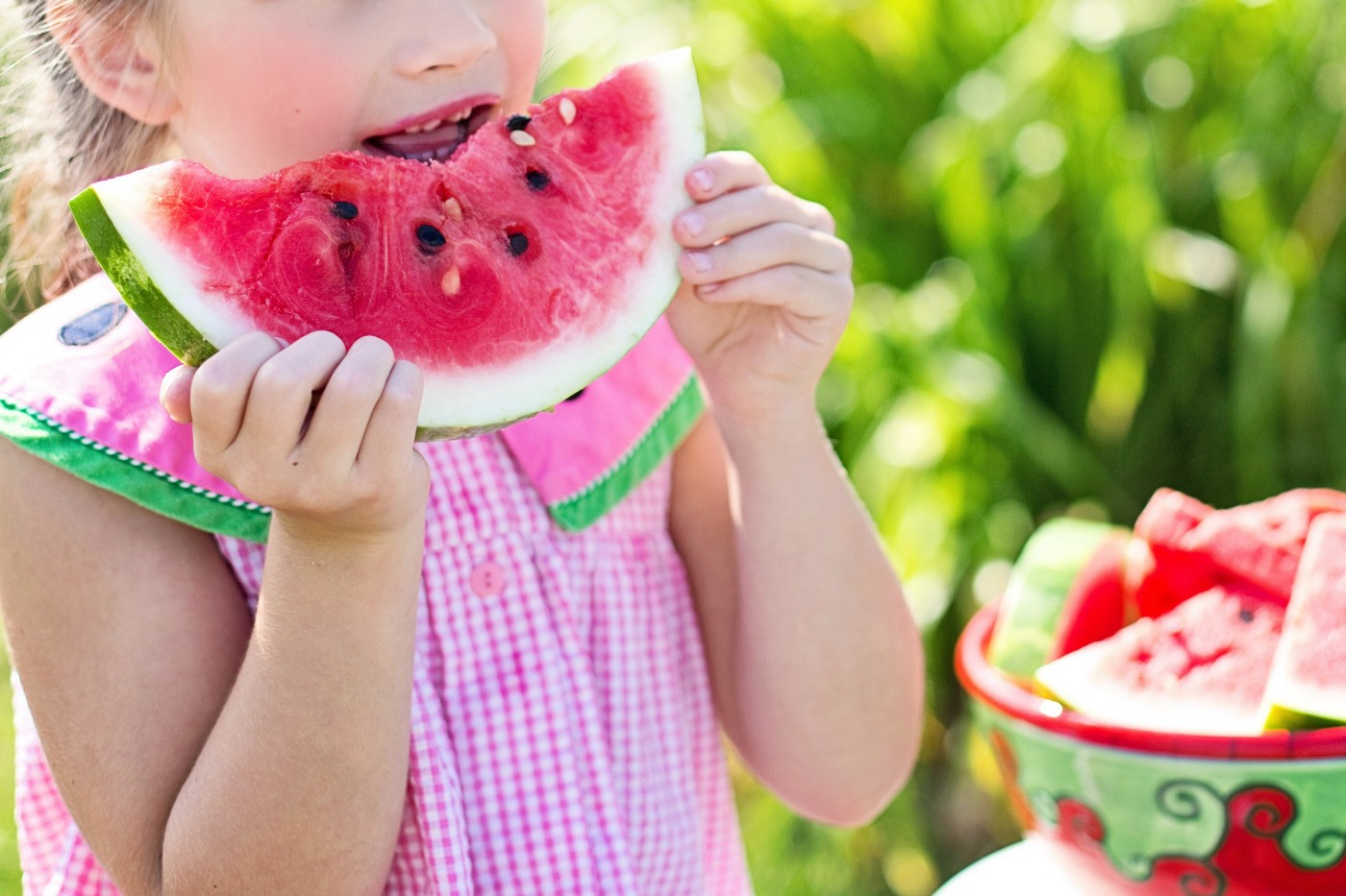 Little girl in a pink dress eating watermelon.