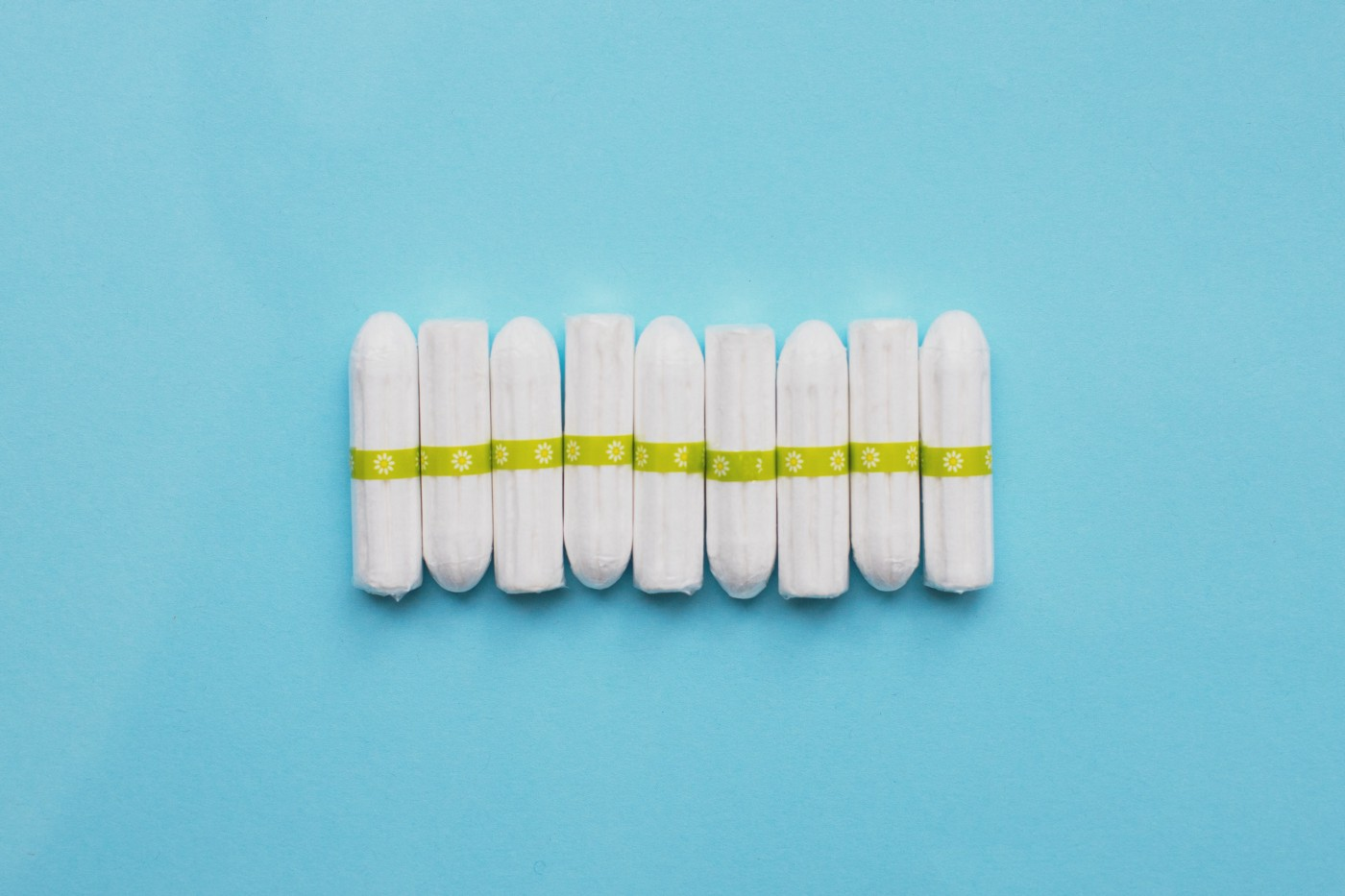Nine tampons are lined up next to each other horizontally on a plain blue background.