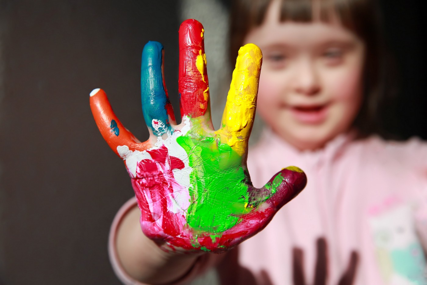A young child with Down syndrome holding up their painted palm to show five painted fingers