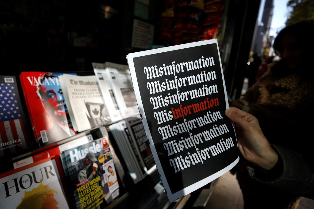 "Misinformation newsstand in Manhattan. Person holds magazine that has ""Misinformation"" on the cover."