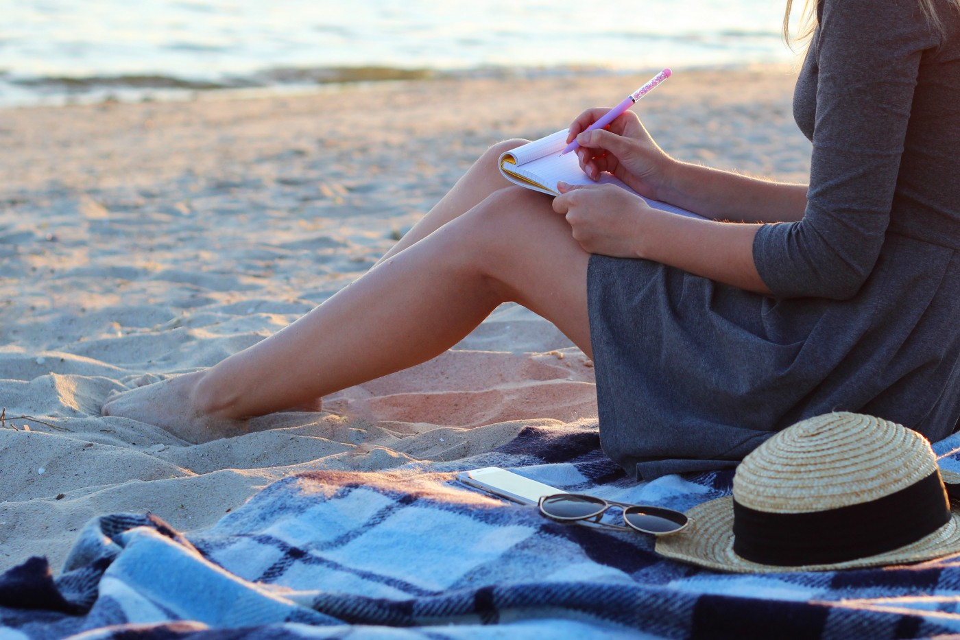 A woman in a grey dress sits on a picnic blanket on the sandy beach, just at the water's edge. She had a straw hat and sunglasses next to her and is writing in a notebook.