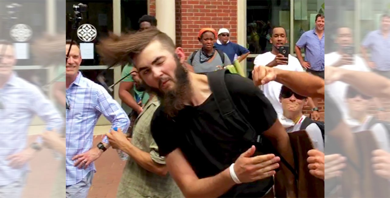 A man in a black shirt standing in the street while holding a shield is punched in the face as bystanders look on with mixed reactions, from laughter to distress.