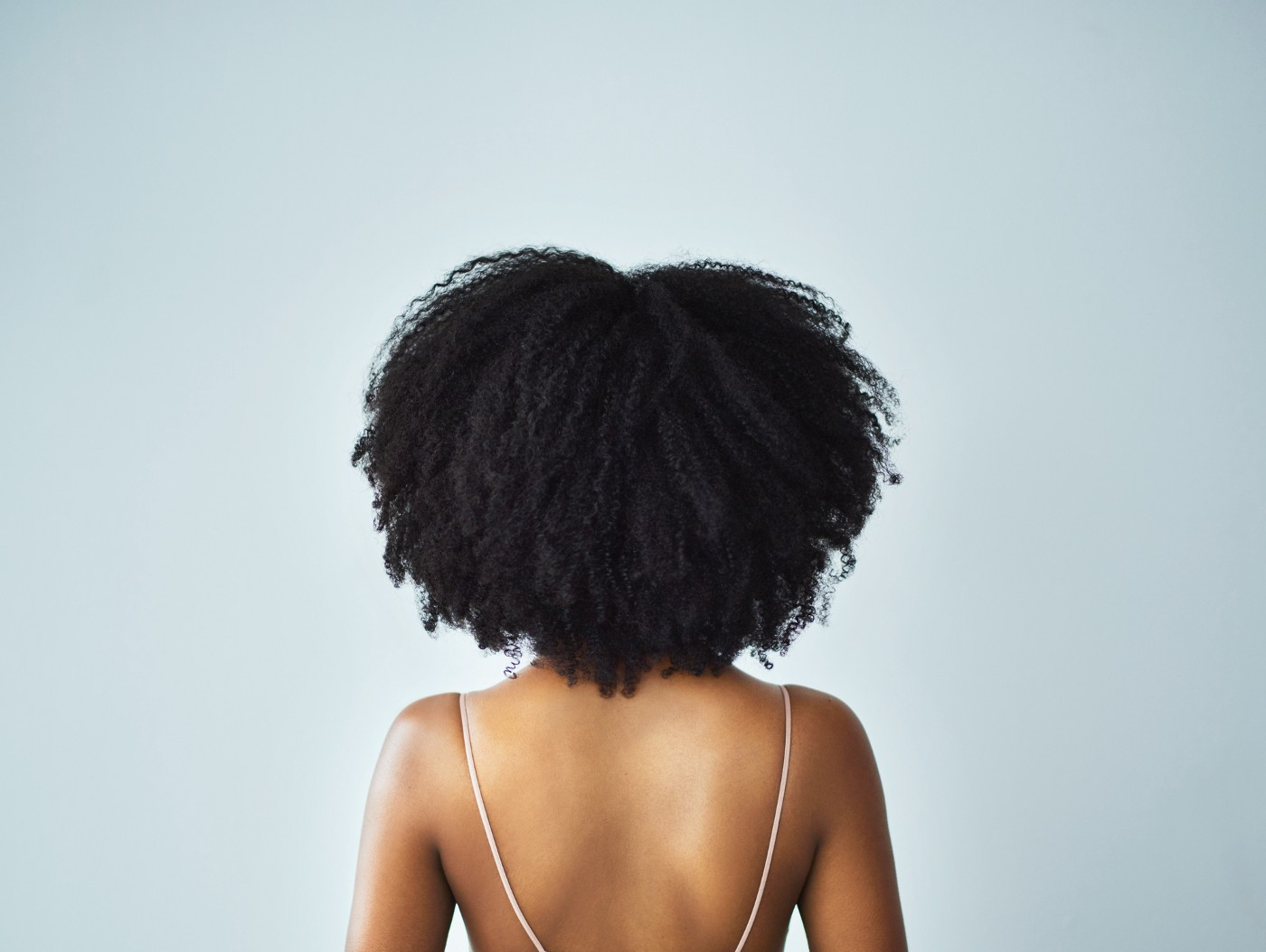 Back view of a Black woman with natural hair.