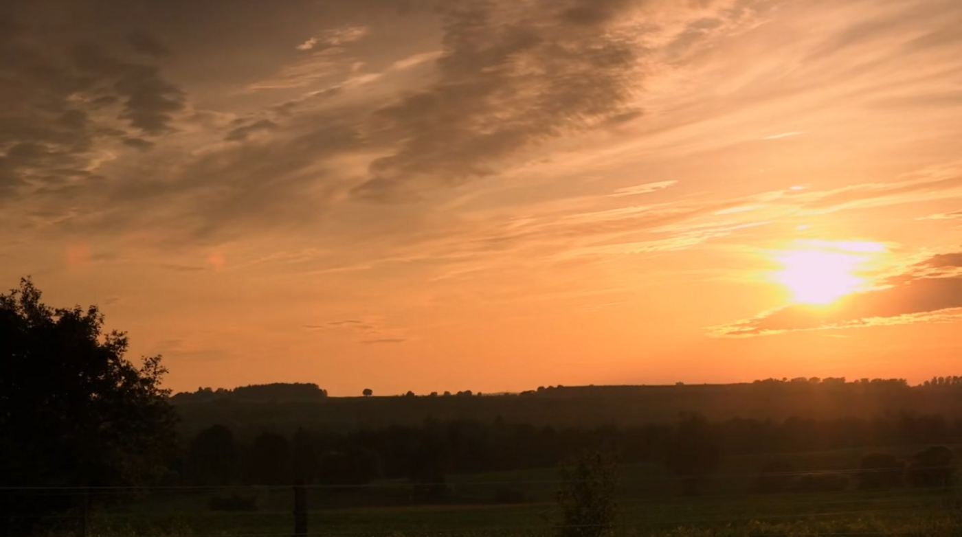 A picture of a sunset over a rural horizon
