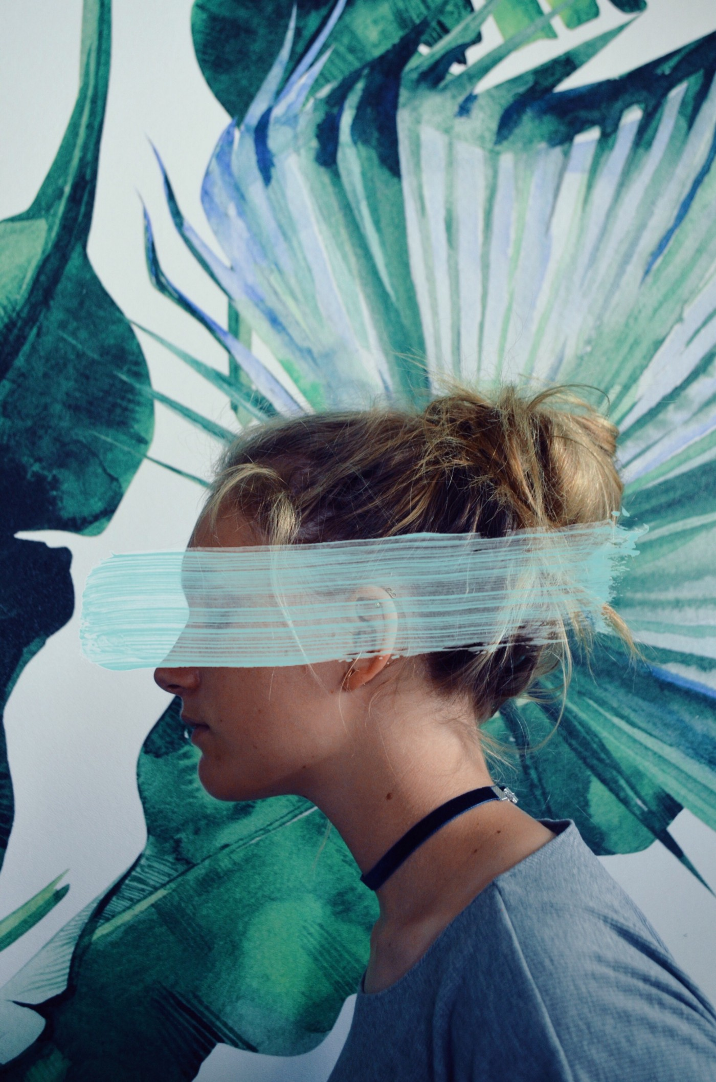 Image of a woman with huge floral painting in the background. her face is partly covered by a large strip of turquoise paint