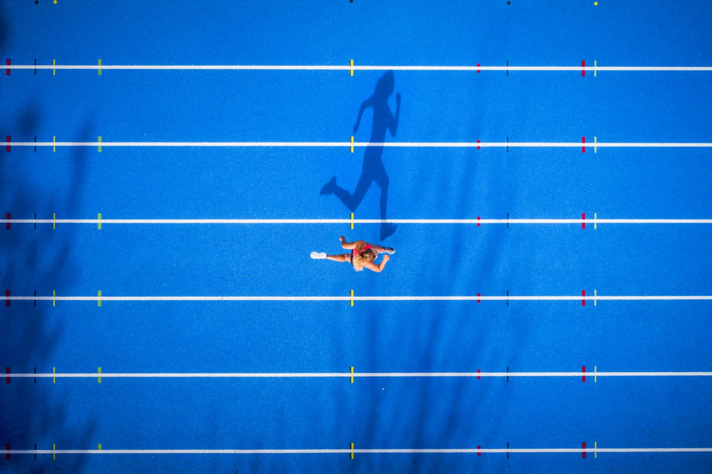 An aerial photo of a person running on a track. Their shadow looks like it's running.