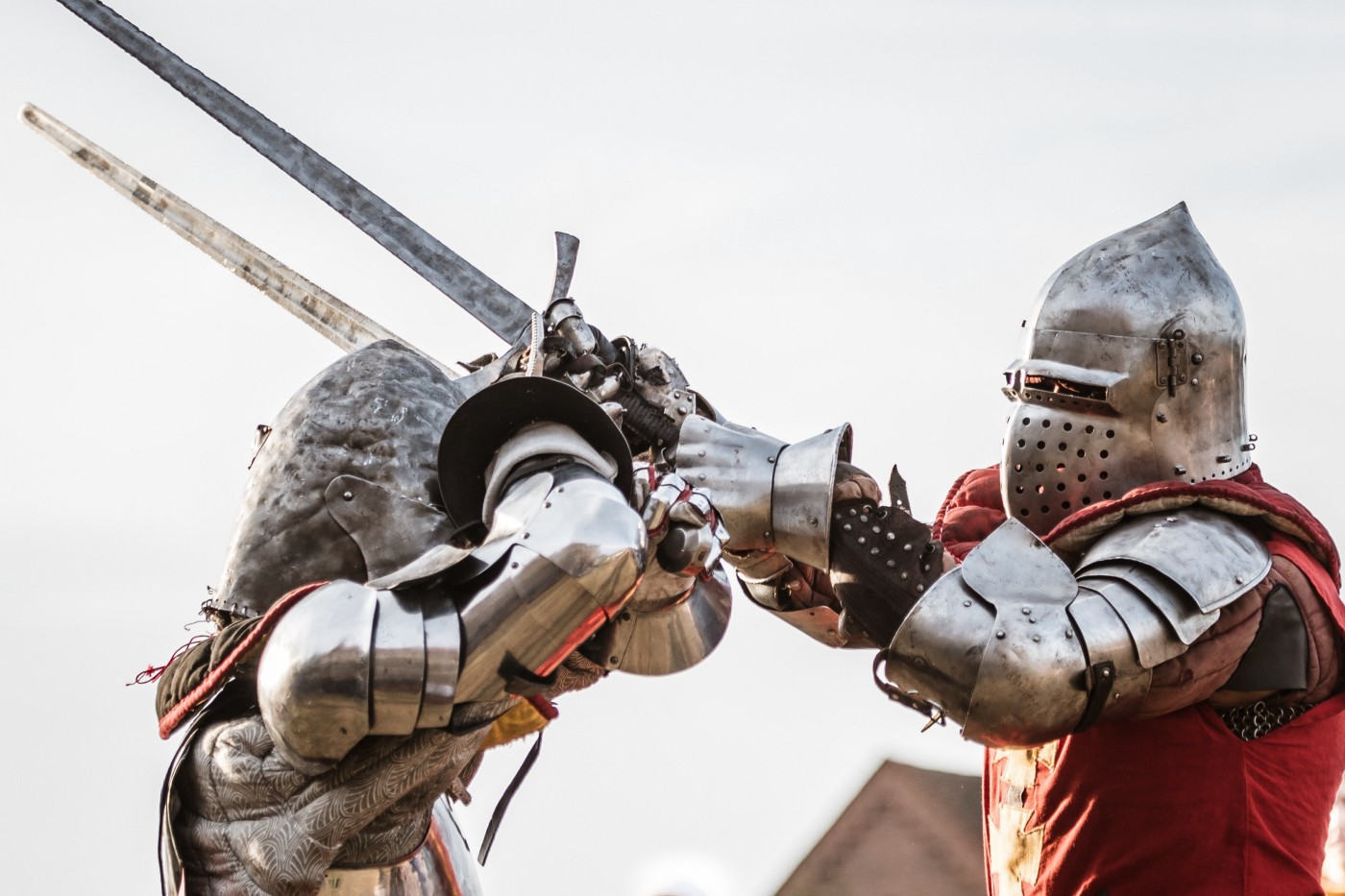 Two knights in plate armor and some chainmail battle in close quarters with broadswords.