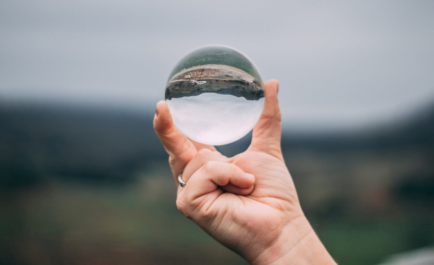 A hand holding up a glass orb in front of a blurred landscape. The landscape viewable in the orb is inverted.