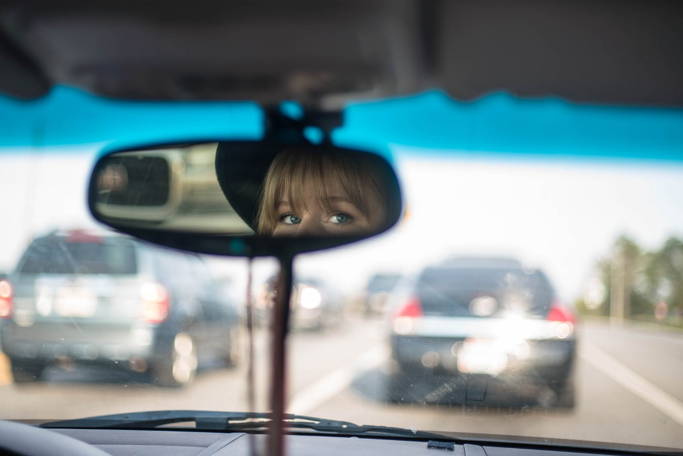 Woman looks at viewer through rear view mirror in car on crowded road