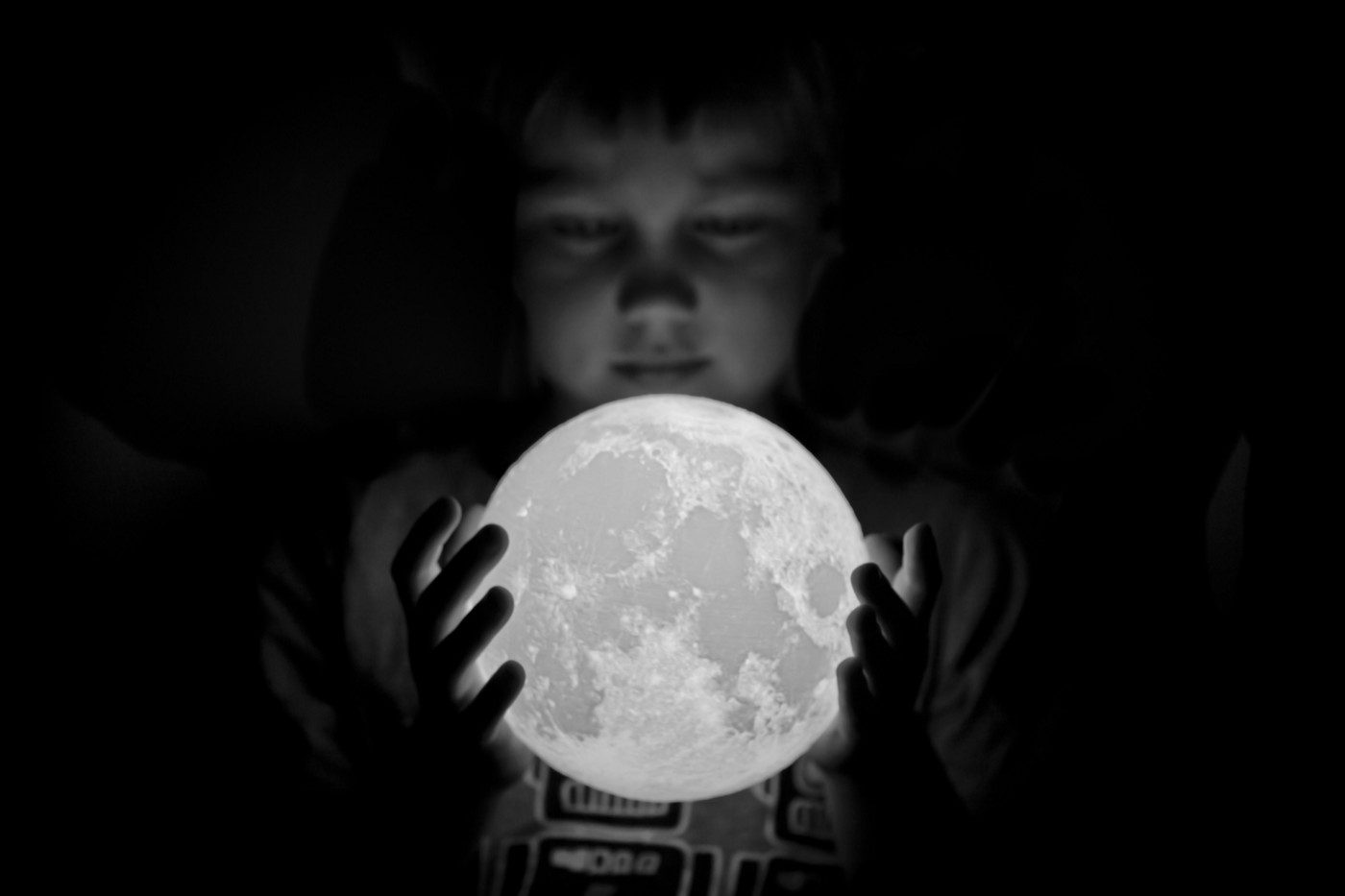 Black and white photo of a young boy holding a moon figure in his hands.