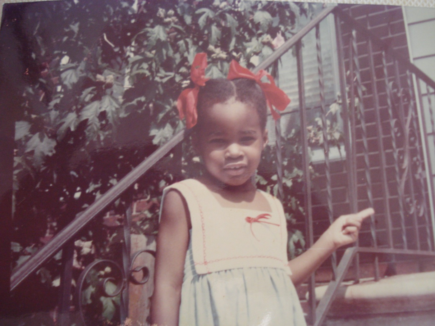 A young, Black girl circa 1983 in a summer dress with two big, red ribbons in her hair.