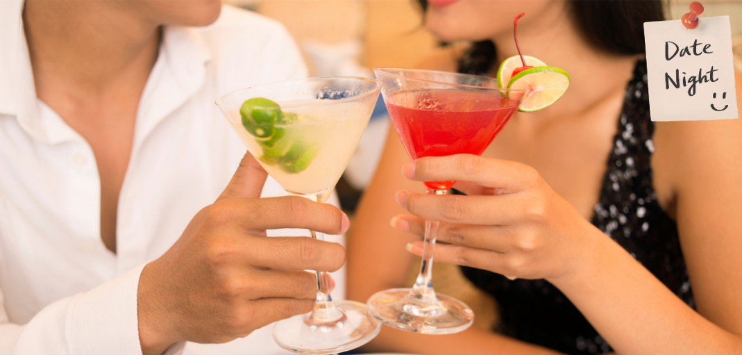 """Date night picture of a man and a woman holding clinking together two cocktails—""""cheers"""""""