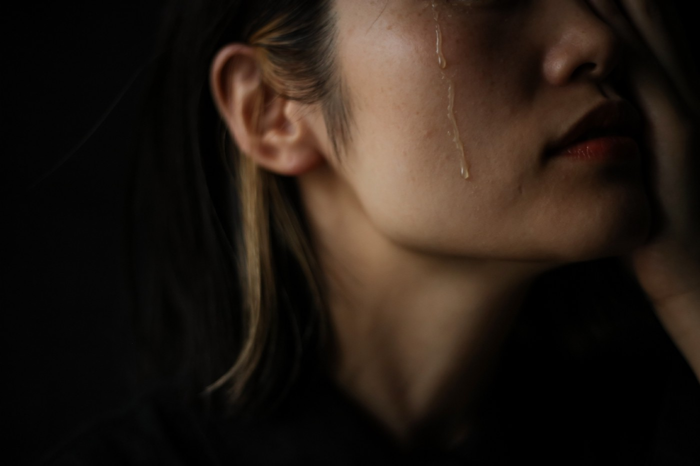 Moody shot of a person with long hair and a tear rolling down their cheek. Their eyes are out of frame.