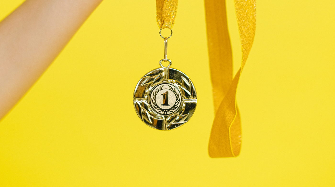 Gold first place medal on a yellow ribbon in front of a bright yellow background